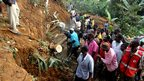 Residents of Bududa cut through trees on 26 June 2012 in an effort to reach the bodies of victims of the previous day's mudslide in the eastern Uganda district of Bududa.