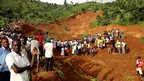 Residents stand on the debris on the site where a landslide swept away three villages in the Bududa district of eastern Uganda on 25 June 2012.