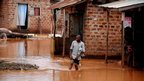 A resident of Kampala wades through flood water in the suburb of Kalerwe on 25 June 2012, after a landslide buried three villages in the Bududa district of eastern Uganda.
