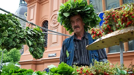A man sells oak-leaf wreaths and wild strawberries in Riga