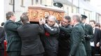 Tyrone GAA members pass the coffin of murdered PSNI officer Ronan Kerr to his police colleagues