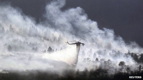A helicopter drops water on the Waldo Canyon fire burning behind the US Air Force Academy, west of Colorado Springs, 27 June 2012
