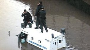 Police on roof of Land Rover