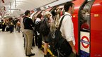 Commuters wait to board a busy London Underground train