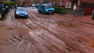 West Belfast estate roads covered in mud from a flood-swollen river