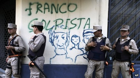 "Police officers stand in front of wall spray painted with a message that reads in Spanish: ""Franco, coupmonger,"" referring to newly named president Federico Franco"