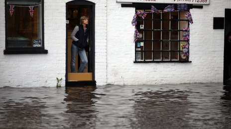 Shop workers look out at flash flooding in the Staffordshire village of Penkridge
