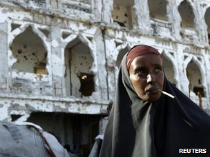A woman walks through the war-damaged streets of Mogadishu (26 June 2012)