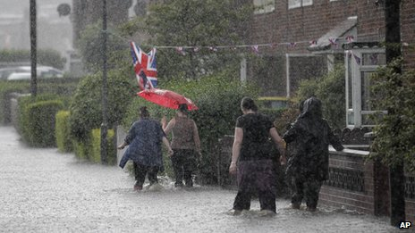 People wade through flood water