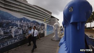 People walk past heavy fences outside the Hong Kong Convention and Exhibition centre where ceremonies marking the 15th anniversary of the handover of Hong Kong will be held, 28 June, 2012