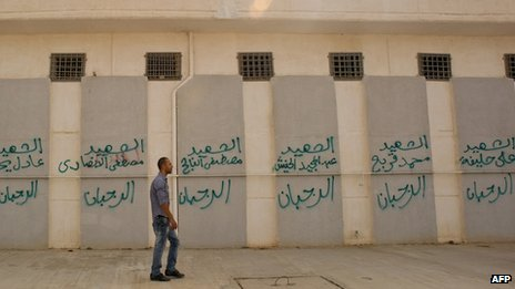 A Libyan man in September 2011 walks past the names of some of those who died at the Abu Salim prison in central Tripoli