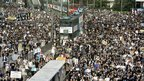 Trams sit stranded as thousands of people block the streets in a huge protest march in Hong Kong, 01 July 2003
