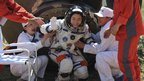 China's first female astronaut Liu Yang waves as she comes out of the re-entry capsule of Shenzhou-9 spacecraft in Siziwang Banner of Inner Mongolia region in northern China, 29 June 2012