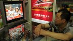 A shop owner watches television in his store in Shanghai as China's first female astronaut Liu Yang is shown getting out of the re-entry capsule of Shenzhou-9 spacecraft, 29 June 2012