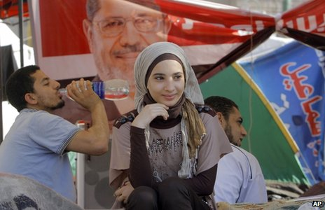 A young woman sits in front of a tent in Tahrir Square decorated with a banner showing the face of Mohammed Mursi (28 June 2012)