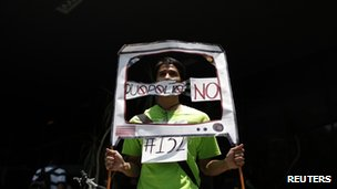 "student from the anti-PRI youth opposition movement ""Yosoy132"" (I am 132) holds a mock TV during a protest at the facilities of telecoms regulator Cofetel"