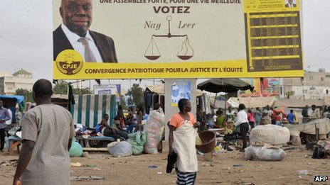 People walk past a hoarding bearing the portrait of a candidate for the Senegalese legislative elections in Dakar