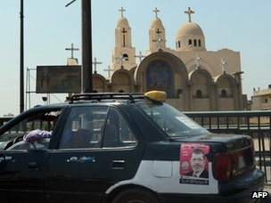 A taxi with a Mursi poster on its body drives past a Coptic church in Cairo