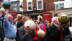 Shrovetide footballs are held aloft in Ashbourne.