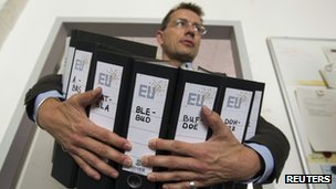 "A member of the non-governmental organisation ""More Democracy"" carries folders with letters of attorney for a constitutional complaint against the ratification of the fiscal pact in Berlin, June 29"