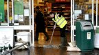 Staff member sweeps away flood water at Waitrose in Hexham, Northumberland. Image by Bob Turner