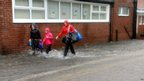 Children walk to school in rain and floodwater in North Tyneside.