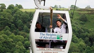 The Olympic flame is carried on a cable car in Matlock