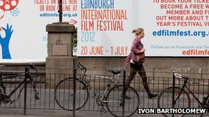 Woman walks past a poster for the EIFF