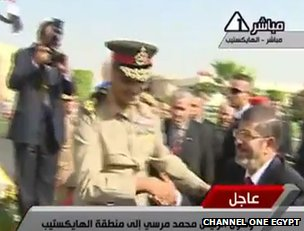 Field Marshal Hussein Tantawi shakes hands with new Egyptian President Mohammed Mursi (video grab from Egyptian public TV broadcaster Channel One)