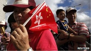 A resident carrying Hong Kong and Chinese flags attends a flag-raising ceremony to mark the 15th anniversary of the territory's handover to Chinese rule, in Hong Kong July 1
