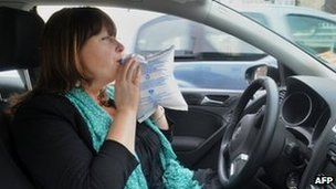 A woman uses a breathalyser (Ethylotest) on June 26, 2012 in the French western city of Quimper
