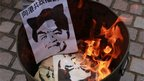Protesters burn pictures of Hong Kong new Chief Executive Leung Chun-ying, saying &quot;tell Hong Kong people to say no to Communist power&quot; in Chinese, during a protest against Mr Leung in Hong Kong on Sunday