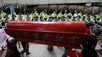 Protesters carry an empty coffin during a protest against visiting Chinese President Hu Jintao in Hong Kong on Sunday