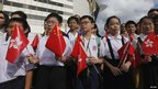 Students carrying Hong Kong and Chinese flags attend a flag-raising ceremony to mark the 15th anniversary of the territory&#039;s handover to Chinese rule, in Hong Kong July on Sunday