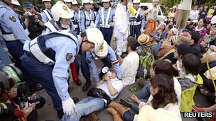 Police try to move a protester at the Ohi nuclear plant in Japan on 1 July 2012