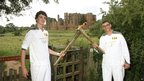 Torchbearer 139 Matthew Watkinson passes the Olympic flame to Charles Krivanek in front of Kenilworth Castle