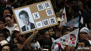 A protester holds a sign mocking new leader Leung Chun-ying during a demonstration urging him to step down in Hong Kong, 01 July 2012