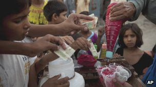 Poor children buy noodles blended in ice in Christian Colony, Islamabad