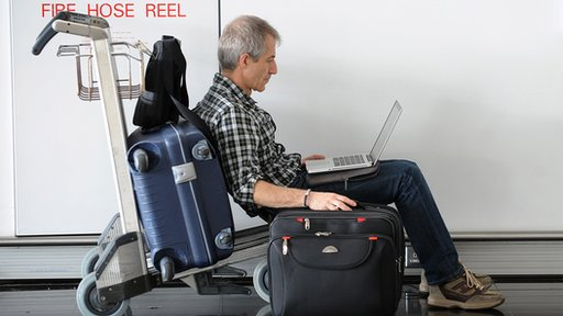Man using a laptop at an airport