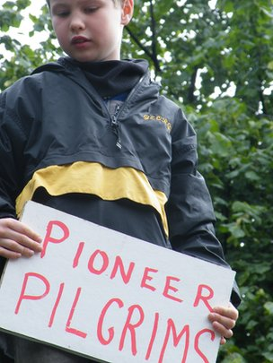 "Small boy holds ""pioneer pilgrims"" sign"