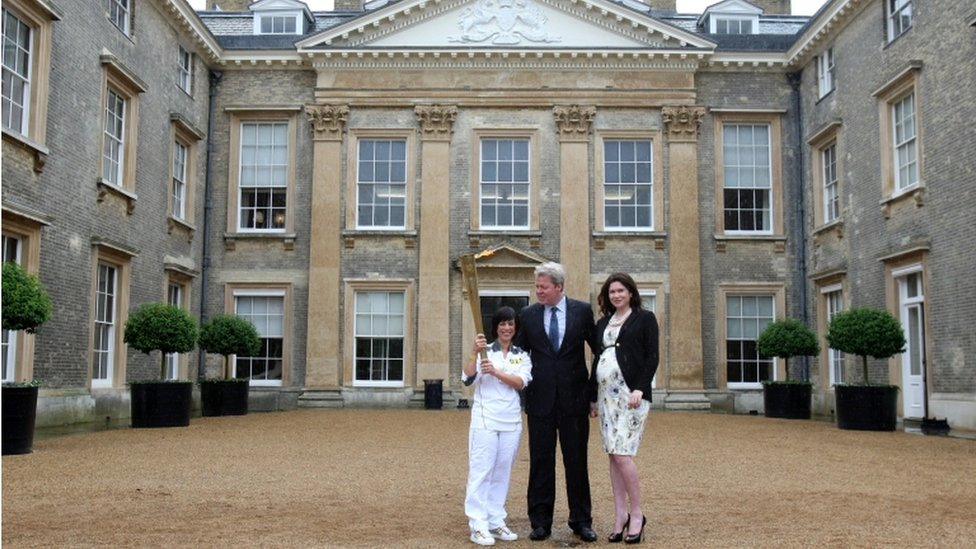 Torchbearer Fiona Warner holds the flame in front of Althorp House ...