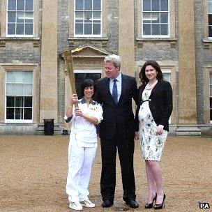 Fiona Warner holds the flame at Althorp House with Earl Spencer and his wife Karen Gordon