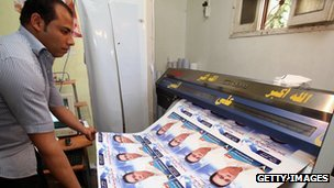 A Libyan worker rolls freshly-printed election campaign posters