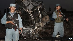Afghan policemen stand guard near a damaged bus at the scene of the suicide attack in Kandahar