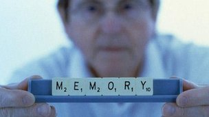 Man holding up scrabble words spelling memory