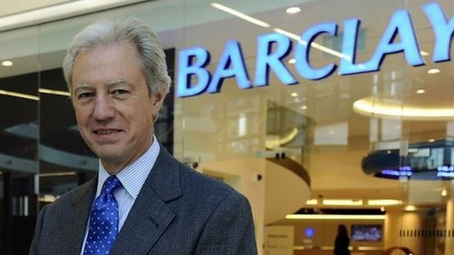 Man standing in front of Barclays sign