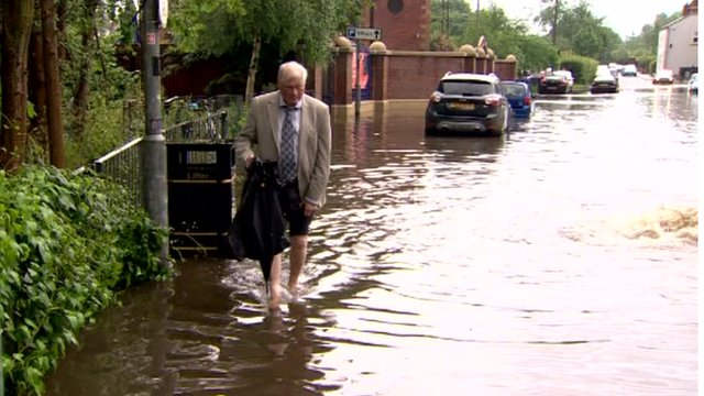 A man walks through flood water