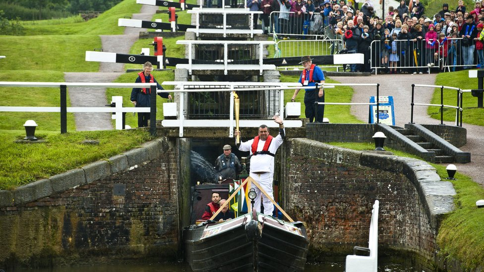 Robert Gomez holding the torch at Foxton Locks.