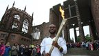 Torchbearer Ali Abdillahi on the steps of Coventry Cathedral