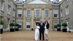Torchbearer Fiona Warner holds the flame in front of Althorp House with Earl Spencer and Karen Gordon